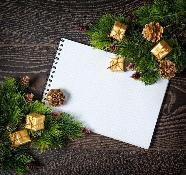 Kerstmisstilleven met een kaart voor gefeliciteerd, nieuwjaarsbal, sparren op oude tafel