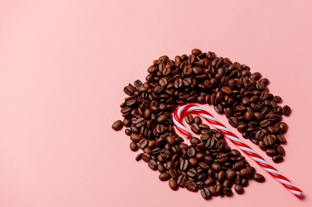 Kerstmissuikergoed en koffiebonen op roze muur