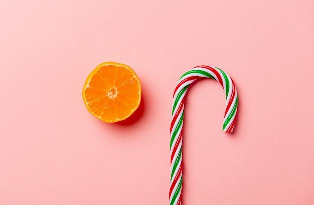 Kerstmissuikergoed en sinaasappel op roze muur