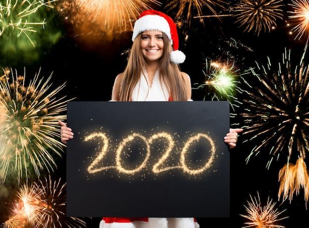 Kerstmisvrouw die een gelukkige 2020 wensenkaart houden