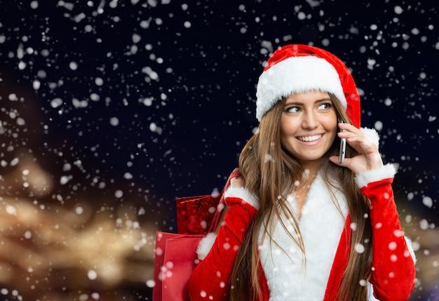 Kerstmisvrouw die telefoneert gebruikend haar mobiele telefoon