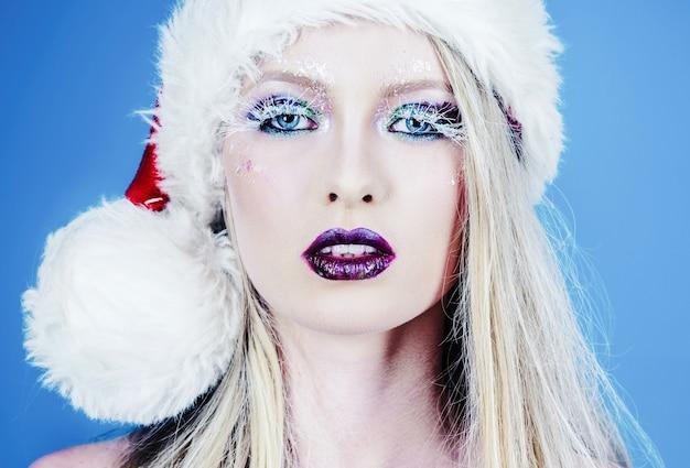 Kerstmisvrouw met vakantiemake-up. schoonheid modelmeisje in kerstmanhoed. close-up portret.