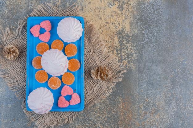 Kerstmiszephyr met geleisuikergoed op een blauw bord. hoge kwaliteit foto