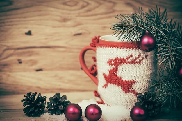 Kerstmok met gebreide hertendecoratie op de houten ondergrond