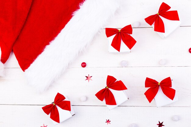 Kerstmuts en geschenken, witte doosjes met rode strik en snoepjes