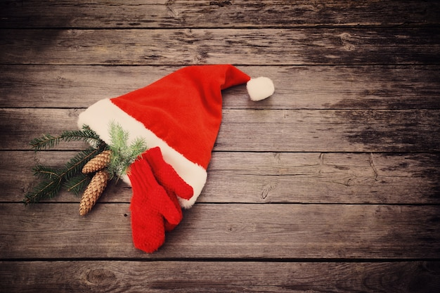 Kerstmuts en rode want op oude houten achtergrond
