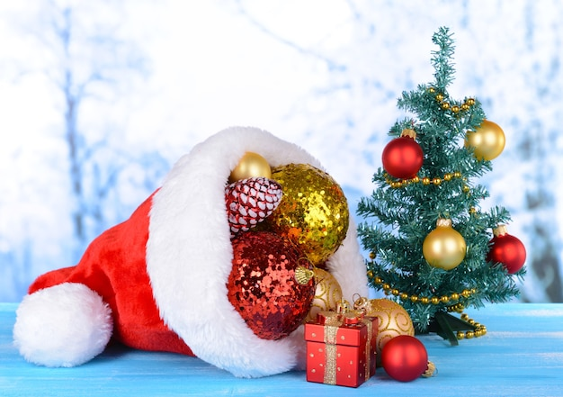 Kerstmuts met kerstversiering op tafel op lichte achtergrond