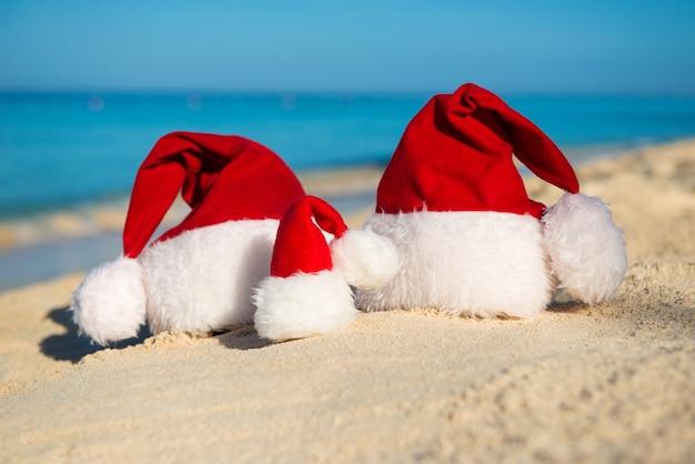 Kerstmutsen op zandstrand - concept van nieuwjaarsvakantie met het gezin met de kinderen aan zee.
