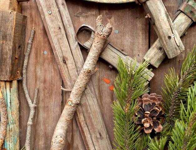 Kerstmuur met takken en dennentakken met dennenappels.
