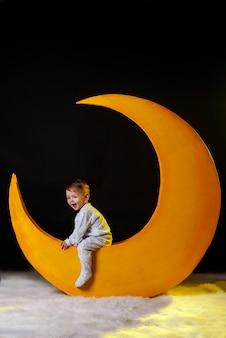 Kerstnacht. babe, de jongen zit op een gele maan in een pyjama