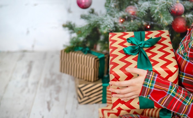 Kerstochtend, meisje met geschenken in haar handen. selectieve aandacht.