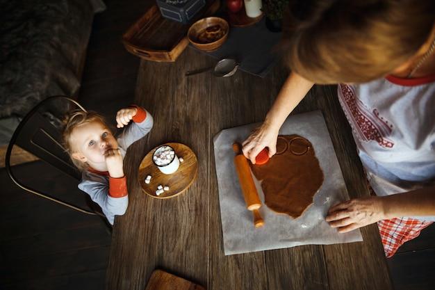 Kerstochtend. oma kookte gemberkoekjes en kleindochter die cacao met marshmallows dronk.