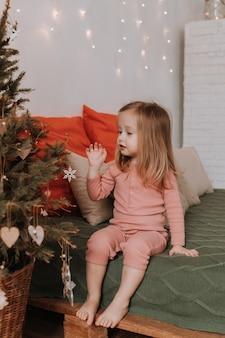 Kerstochtend zit een klein meisje in roze pyjama op het bed bij de kerstboom