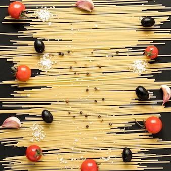 Kerstomaat; zwarte olijven; teentjes knoflook; blackpepper gerangschikt op rauwe spaghetti