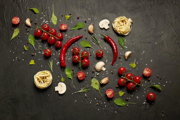 Kerstomaatjes, rode paprika, knoflook, champignons, pasta, rucolablaadjes en kruiden op zwart