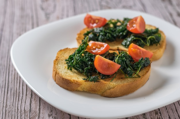 Kerstomaten en geroosterde greens op sneetjes brood op een houten tafel. vegetarische snack.