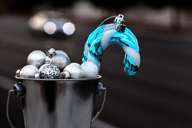 Kerstornamenten verzameld in zilveren emmer voor het versieren van kerstboom