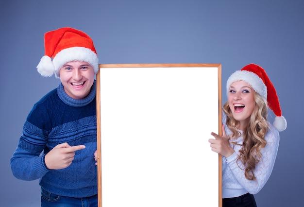 Kerstpaar met wit bord met lege kopieerruimte