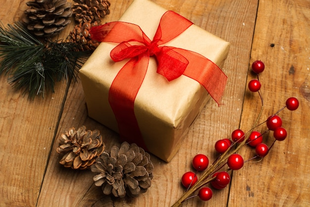 Kerstpakket met een rode strik op een rustieke houten tafel