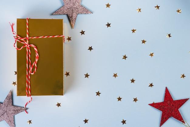 Kerstpatroon gemaakt van gouden, zilveren, rode sterren met gouden geschenkdoos op blauw