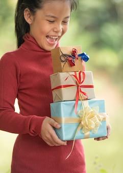 Kerstportret van een gelukkig lachend klein meisje met een geschenkdoos in de buurt van een groene takboom. groene bladeren bokeh onscherp achtergrond van natuur bos.