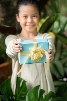 Kerstportret van een gelukkig lachend klein meisje met een geschenkdoos in de buurt van een groene takboom.