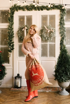Kerstportret van een meisje in een roze jurk en een jas van schapenvacht met een kerstdecor met een rode tas met geschenken. een vrouw bereidt zich voor om kerstmis en nieuwjaar te vieren