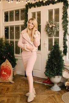 Kerstportret van een meisje in een roze jurk en schapenvachtjas met het kerstdecor van het huis in een elegant interieur. een vrouw bereidt zich voor om kerstmis en nieuwjaar te vieren