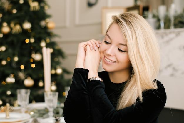Kerstportret van een meisje in een zwarte jurk van het kerstdecor