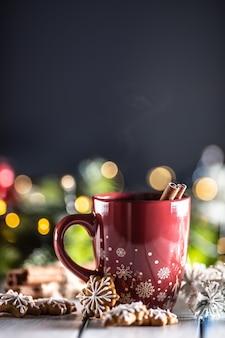 Kerstpunch in een rode kop met peperkoekkaneel en decoraties voor de feestdagen.