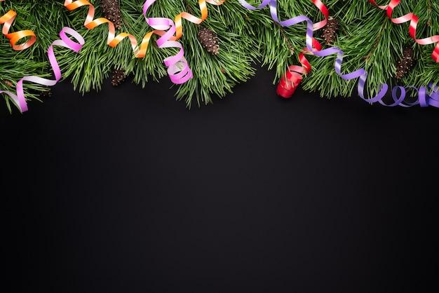 Kerstrand met dennentakken en feestelijke slingers op een zwarte achtergrond