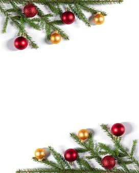 Kerstrand van dennentakken, gouden en rode ballen op een witte achtergrond. verticale oriëntatie.