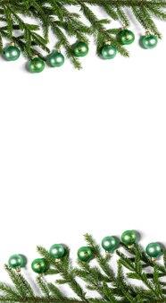 Kerstrand van natuurlijke sparren takken en groene ballen op een witte achtergrond