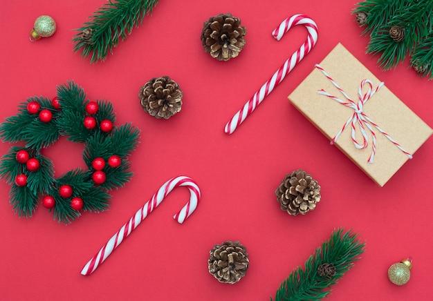 Kerstrood met twee zuurstokken, kerstkrans, geschenkdoos, dennenappels, decoraties.