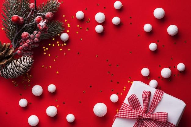 Kerstrood met witte sneeuw ornamentdecoratie, sparrentak en geschenkdoos