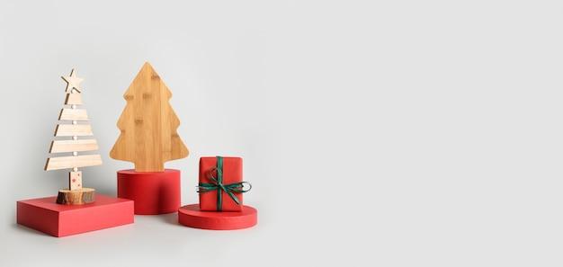 Kerstrood staat met cadeau en decoratieve houten creatieve kerstboom als banner voor wenskaart. moderne podium achtergrond.