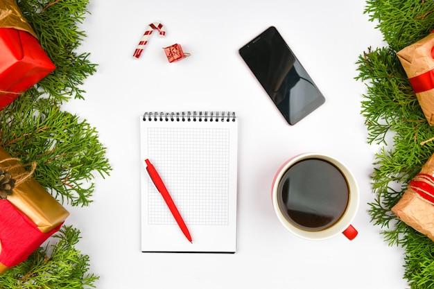 Kerstruimte van kladblok, telefoon, koffiemok. keramische rode beker met zwarte koffie. nieuwjaars lay-out. uitzicht van boven. een vrouwelijke hand schrijft in een notitieboekje van aderen.