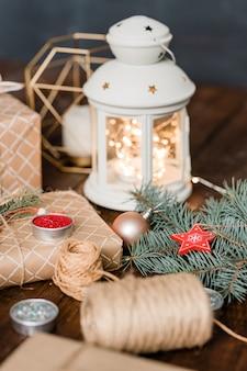 Kerstsamenstelling die bestaat uit lantaarn met brandende kaars erin, ingepakte geschenkdozen, draden, naaldbomen en speelgoedversieringen