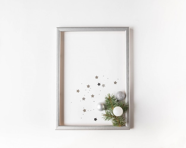Kerstsamenstelling in een zilveren lijst met een vuren tak en zilveren kerstballen en confetti