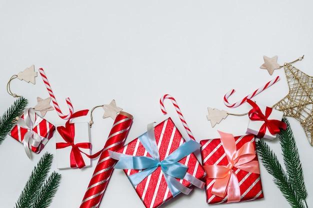 Kerstsamenstelling met geschenkdozen, takken fir tree, papierrollen en decoraties op lichte achtergrond.