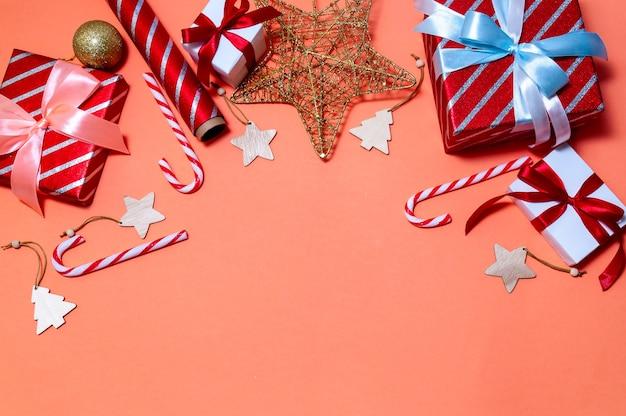 Kerstsamenstelling met geschenkdozen, takken fir tree, papierrollen en decoraties op rode achtergrond.
