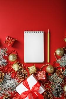 Kerstsamenstelling met kladblok en een potlood voor het schrijven van wensen met kerstboomversieringen