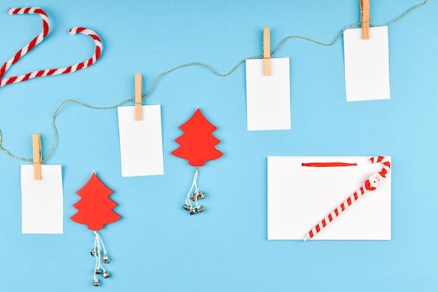 Kerstsamenstelling met verschillende objecten om te schrijven. studio die over kerstmisruimte is ontsproten. lay-out met lege bladeren. plaats om te schrijven. uitzicht van boven. op een blauwe ruimte.