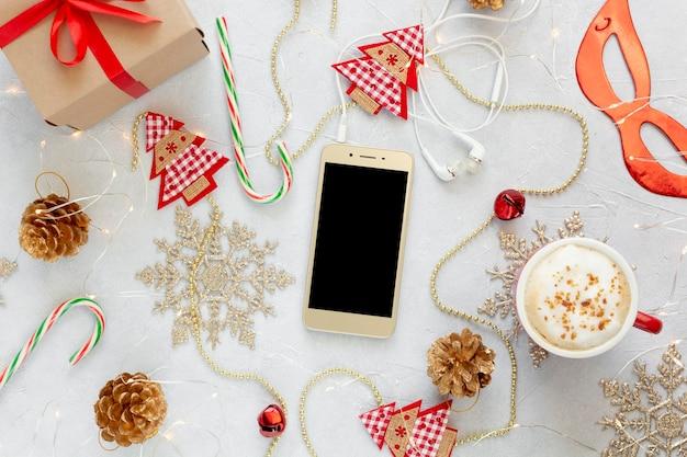 Kerstsamenstelling plat lag met telefoon, koffiekopje en decoraties.