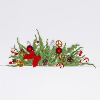 Kerstsamenstelling van naaldtakken, decoraties en snoepjes. plat leggen. bovenaanzicht natuur nieuwjaar concept. kopieer ruimte.