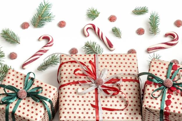 Kerstsamenstelling van verschillende geschenkdozen verpakt in knutselpapier en versierd met satijnen linten. bovenaanzicht, plat gelegd. witte muur.