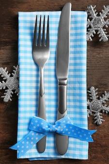 Kerstserveerbestek met servet op een houten oppervlak, close-up