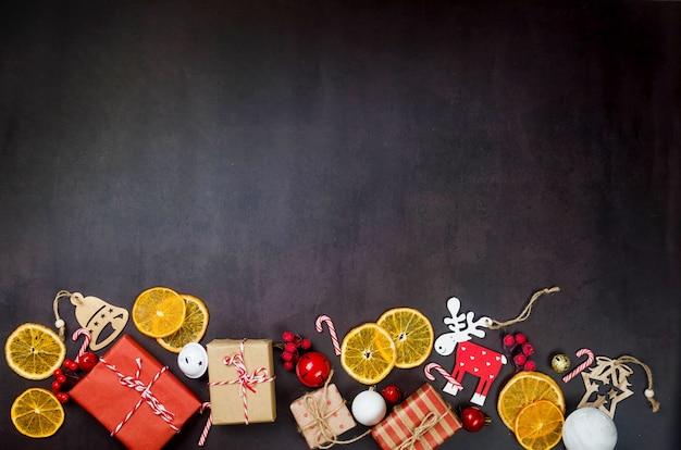 Kerstset met cadeaus verpakt in kraftpapier, houten speelgoed voor de kerstboom, droge sinaasappels