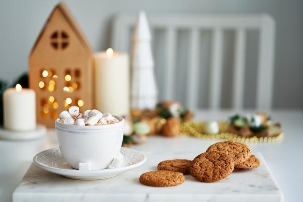 Kerstsfeer in huiskamer feestelijk huis zelfgemaakte chipkoekjes en kop warme chocolademelk