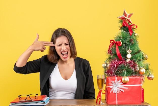 Kerstsfeer met boze gespannen emotionele zakelijke dame zittend aan een tafel in het kantoor op geel
